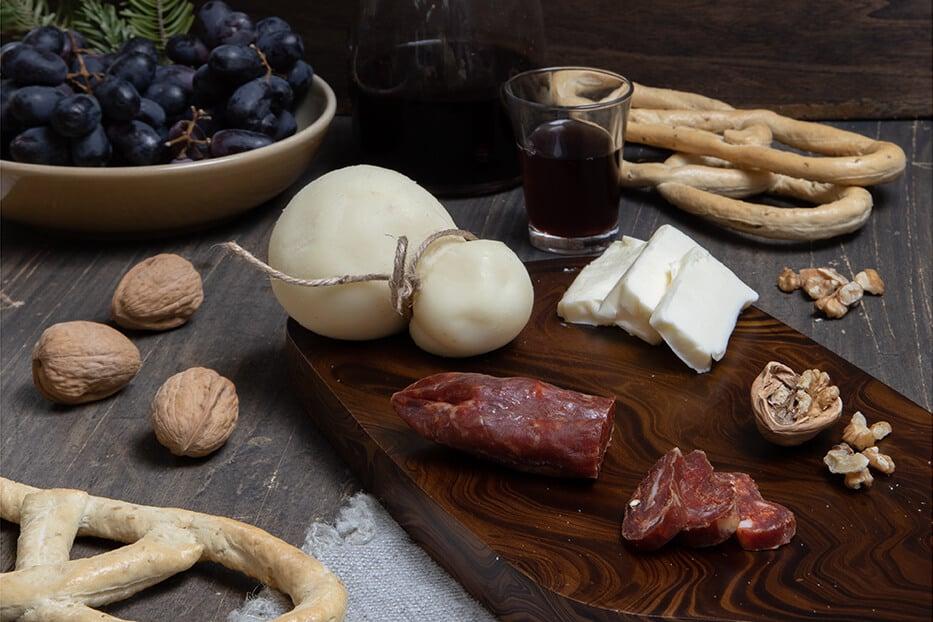 il biscotto a otto su tagliere con formaggi, salsiccia e un bicchiere di vino